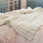 The Macarla Blanket (by Homelea Lass) lying on a bed ready to be snuggled. It can be custom designed to suit your needs.